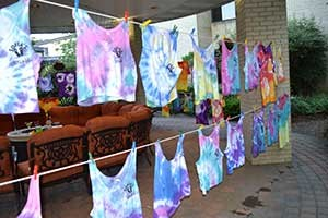 tie-dye tees drying on a clothes line