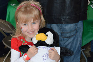 Young girl with her fill-a-friend stuffed animal penguin.