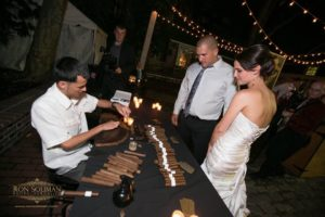 Guests watching a cigar roller create hand-made cigars for them at a party.